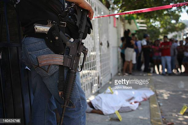Policeman watches a sheet-covered body at a suspected drug-related double execution on March 2, 2012 in Acapulco, Mexico. Drug violence has surged in...