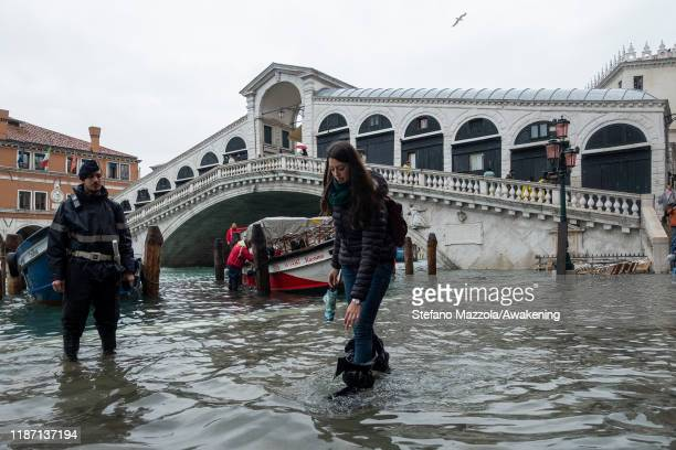 A policeman watches a tourist walking in the water near the Rialto bridge on November 12 2019 in Venice Italy High tide or acqua alta as it is more...