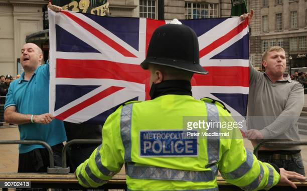 A policeman watches as supporters of the right wing English Defence League chant as a Muslim demonstration passes in Picadilly on September 13 2009...