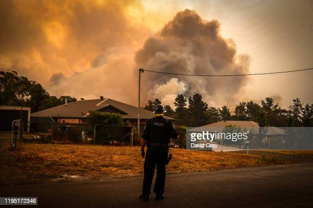 A policeman watches bushfires as they approach homes located on the outskirts of the town of Bargo on December 21 2019 in Sydney Australia A...