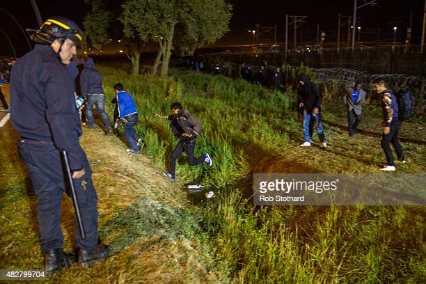 A policeman watches men move away from a security fence beside train tracks near the Eurotunnel terminal in Coquelles on August 3 2015 in Calais...