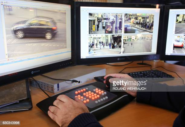 A policeman watches monitors displaying images delivered by surveillance cameras in the Marxloh district of Duisburg western Germany on December 21...