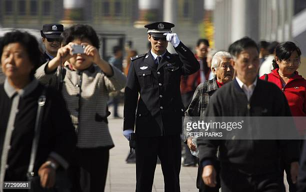 Policeman watches people on Tiananmen Square in Beijing, 12 October 2007, ahead of the 17th National Congress of the Communist Party of China. Police...
