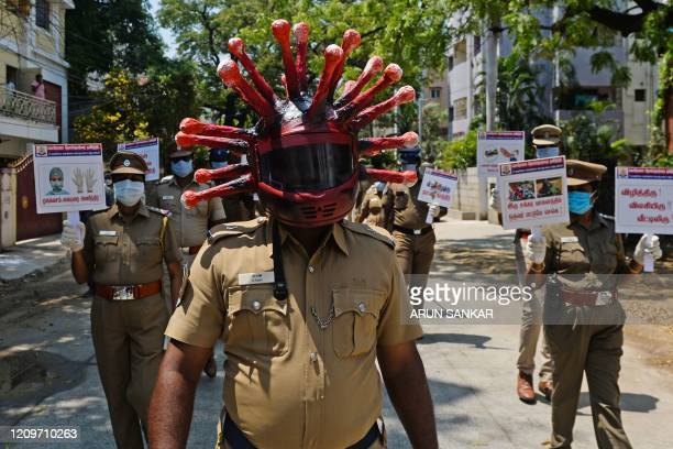 A policeman wearing a coronavirus helmet takes part with others in a procession to raise awareness about the COVID19 coronavirus during a...