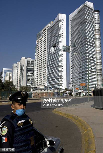 A policeman wearing a face mask guards a bank in Santa Fe an exclusive business area of Mexico city on May 04 2009 The mexican economy received the...