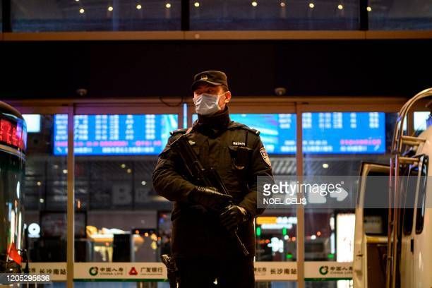 Policeman wearing a facemask as a preventive measure against the spread of the COVID-19 coronavirus stands on guard at the Changsha railway station...