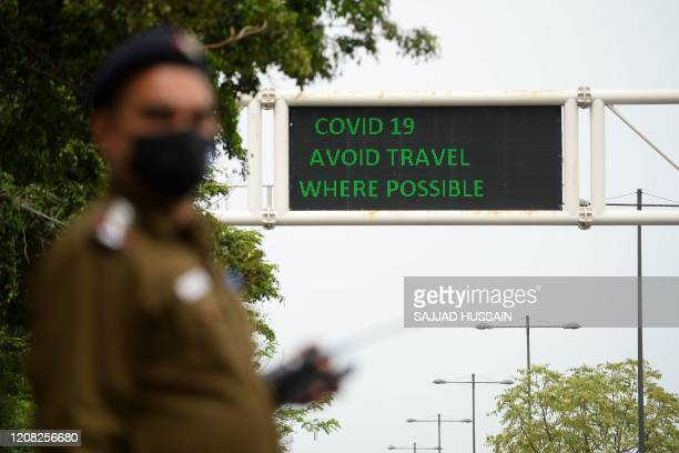 A policeman wearing a facemask stands along a roadsign informing of travel recommendations during a governmentimposed nationwide lockdown as a...