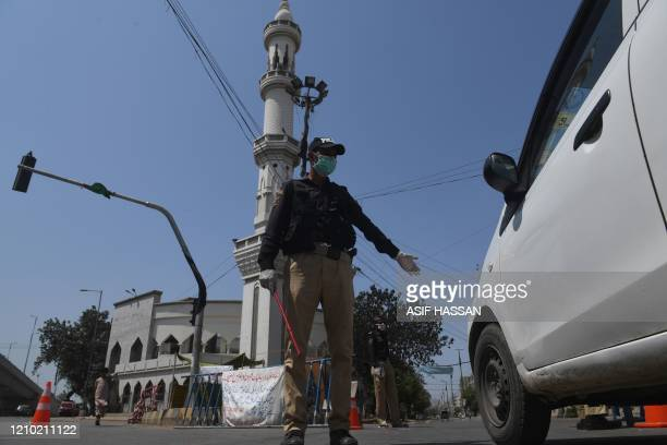 Policeman wearing a facemask stop a commuter beside a closed mosque during Friday prayers on a government-imposed nationwide lockdown as a preventive...