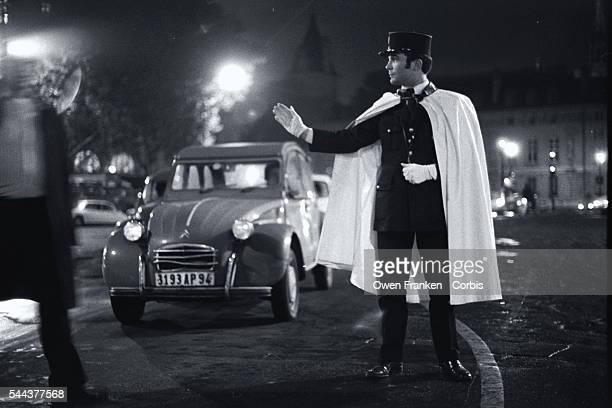 A policeman wearing a white cape directs traffic on the Champs Elysees on New Year's Eve