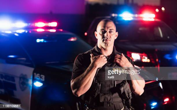 policeman wearing bulletproof vest, by patrol car - police force stock pictures, royalty-free photos & images