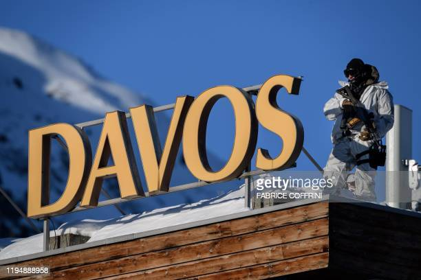 A policeman wearing camouflage clothing stands on the rooftop of a hotel near the Congress Centre during the World Economic Forum annual meeting in...