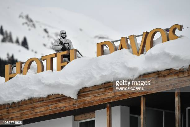 A policeman wearing camouflage clothing stands on the rooftop of a hotel next to letters covered in snow reading Hotel Davos near the Congress Centre...