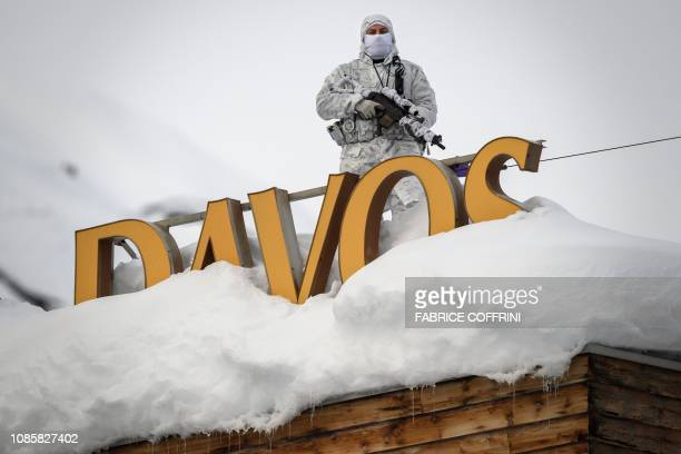 A policeman wearing camouflage clothing stands on the rooftop of a hotel next to letters covered in snow reading 'Davos' near the Congress Centre...