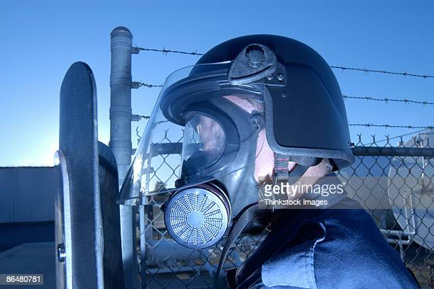 Policeman wearing gas mask and holding shield