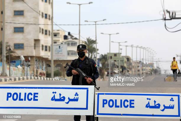A policeman wearing protective gear as a precaution against COVID19 coronavirus disease and loyal to the Palestinian Islamist Hamas movement stands...