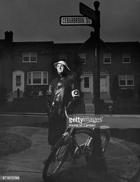 policeman wearing raincoat standing on street - westers schrift stockfoto's en -beelden