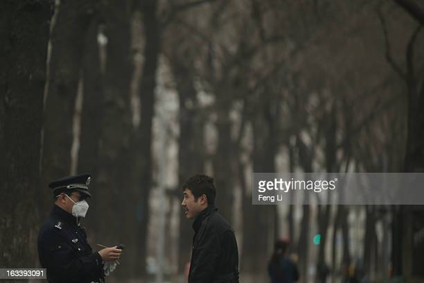 A policeman wearing the mask checks a man's identity card near the Tiananmen Square during the sandstorm on March 9 2013 in Beijing China Strong...