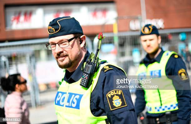 A policeman wears a rose on his uniform as he patrols on April 9 2017 close to the point where a truck drove into a department store in Stockholm...