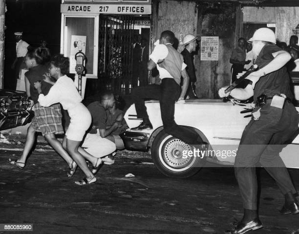 A policeman wields a billy club against youths African American during night of riots in Harlem New York on July 20 1964 The Harlem Riot of 1964 is...