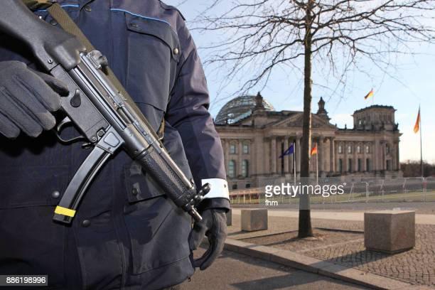 policeman with a machine gun in front of the reichstag (berlin, germany) - demokratie stock-fotos und bilder