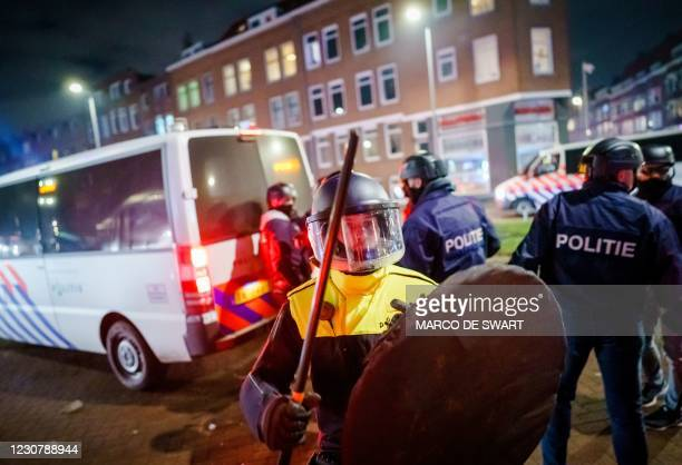 Policeman with helmet and shield holds a baton as he stands next to a policevan on Beijerlandselaan in Rotterdam, on January 25, 2021. - The...