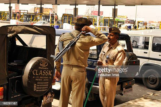 A policeman with his gun near a site of farmers protest against the rollback of toll hike by DelhiNoida Direct flyway on April 2 2013 in Noida India...