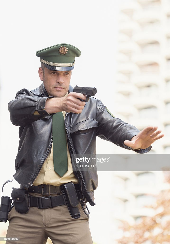 Policeman with pistol making stop gesture : Stock Photo