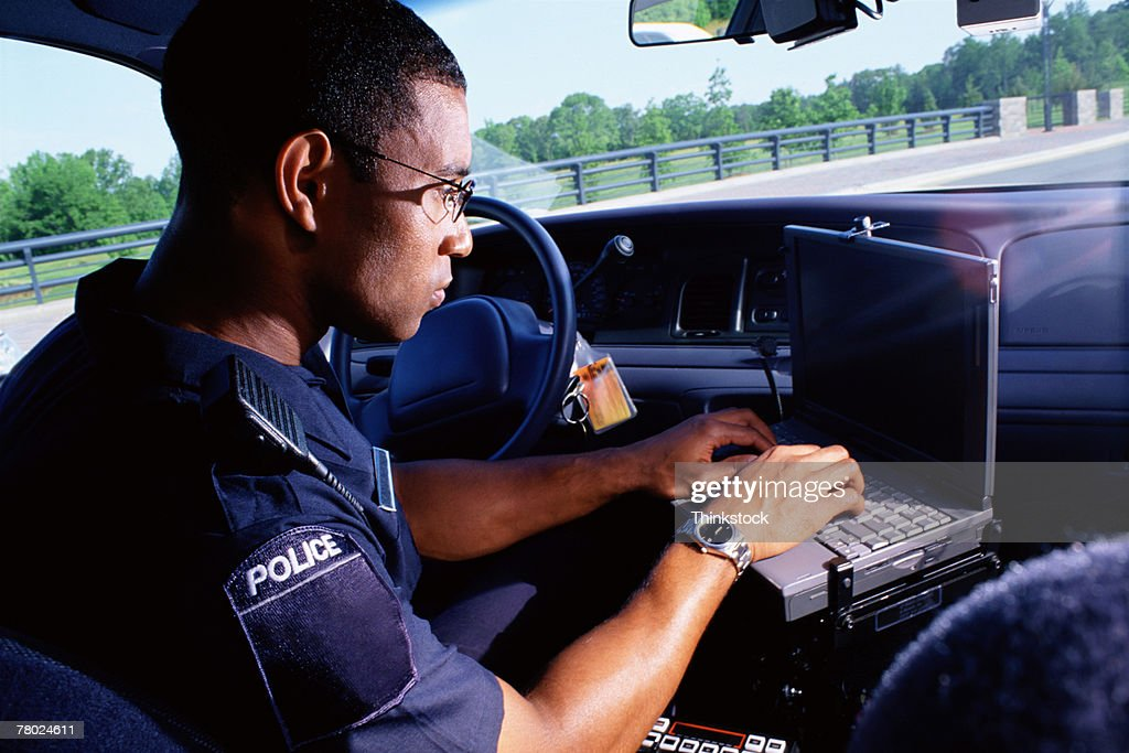 Policeman working on computer in car : Stock Photo