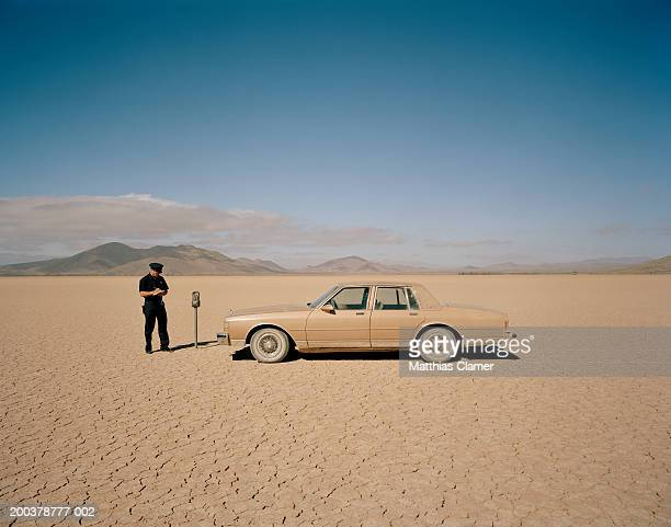 policeman writing parking ticket for car at expired meter in desert - irony stock pictures, royalty-free photos & images