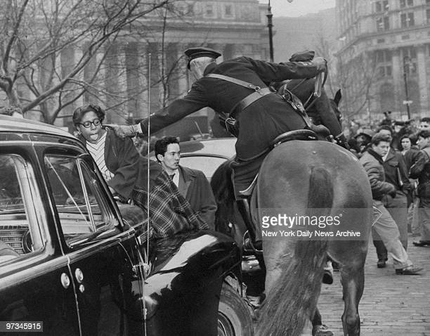 Policeman yanks girl from car at Foley Square after full scale riots ensued during protest on behalf of teachers requesting higher pay