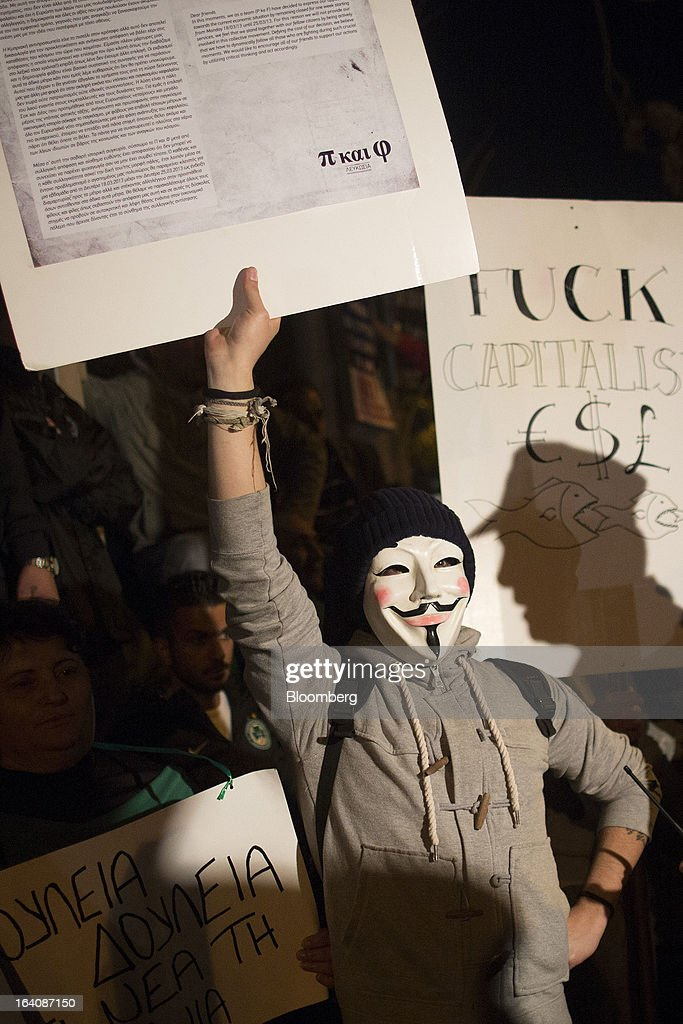 A policeman's shadow is seen against a placard as a demonstrator protests against bank deposit tax plans outside the parliament in Nicosia, Cyprus, on Tuesday, March 19, 2013. Cyprus's parliament rejected an unprecedented levy on bank deposits, dealing a blow to European plans to force depositors to shoulder part of the country's rescue in a standoff that risks renewed tumult in the euro area. Photographer: Simon Dawson/Bloomberg via Getty Images