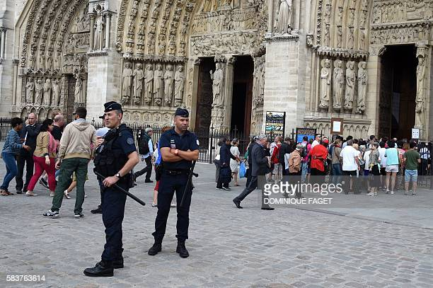 Policemem stand guard in front of the Notre Dame Cathedral as people wait in line prior to a Mass with the archbishop of Paris to pay tribute to the...
