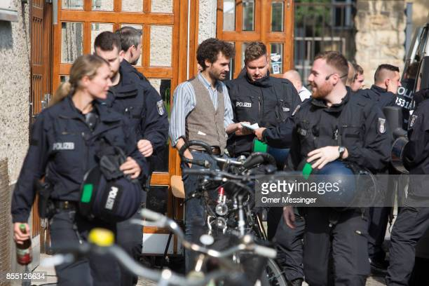 Policemen accompany an activist out of the Volksbuehne theater during negotiations to end the occupation of parts of the theater by activists on...