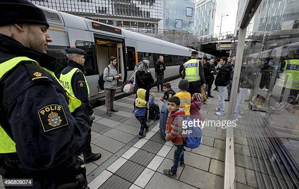 Policemen and a group of migrants stand on the platform at the Swedish end of the bridge between Sweden and Denmark in Malmo Sweden on November 12...