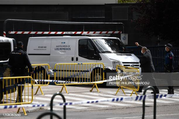 Policemen and an undertaker wearing face masks give instructions to a van arriving at the Palacio de Hielo shopping mall where an ice rink was turned...
