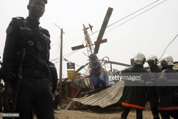 TOPSHOT Policemen and fireman are at workat the site where a helicopter that crashed into a store injuring four people on December 14 2017 near...