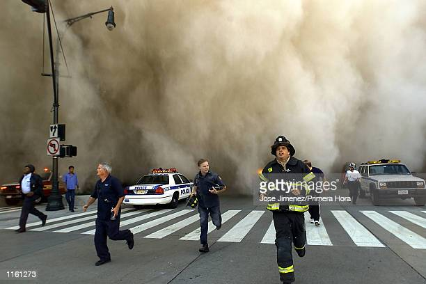 Policemen and firemen run away from the huge dust cloud caused as the World Trade Center's Tower One collapses after terrorists crashed two hijacked...