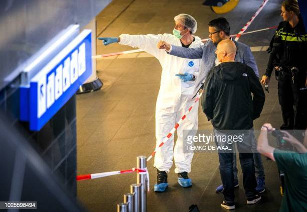Policemen and forensics are at work after a stabbing incident at the central station in Amsterdam on August 31 2018 The Police have shot a suspect...