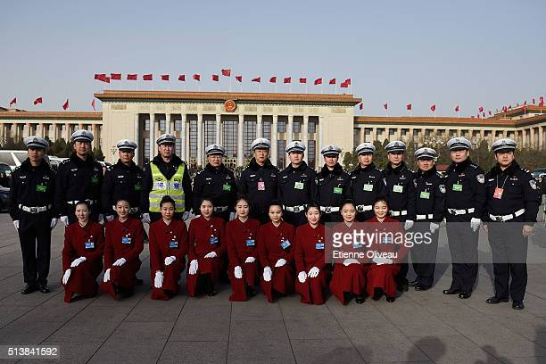Policemen and hotel staff pose in front of the Great Hall of the People during the opening session of the China's National People's Congress on March...