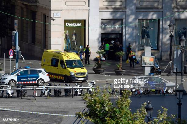Policemen and medical staff members stand in the entrance of a mall after a van ploughed into the crowd killing two persons and injuring several...
