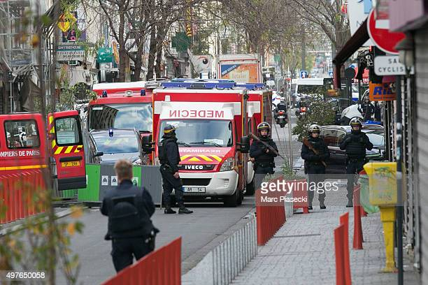 Policemen and medical vehicules are seen on 'Rue Gabriel Peri' on November 18, 2015. French Police special forces raid an appartment, hunting those...