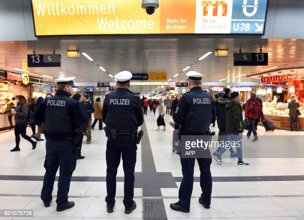 Policemen and passengers are seen in the main train station of Duesseldorf western Germany on March 10 one day after German police have arrested an...