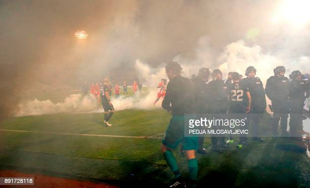 Policemen and players are engulfed in smoke after two groups of Partizan Belgrade's hooligans clashed with each other during the Serbian Superleague...