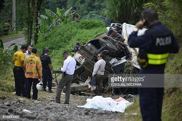 Policemen and rescue officials check the site where a bus plunged off a steep road killing 11 and injuring 12 in Heredia Vara Blanca Costa Rica on...
