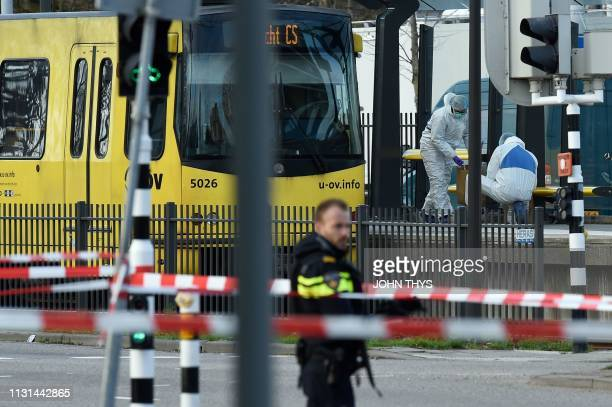 Policemen and rescuers are at work on March 18 2019 in Utrecht near a tram where a gunman opened fire killing at least three persons and wounding...