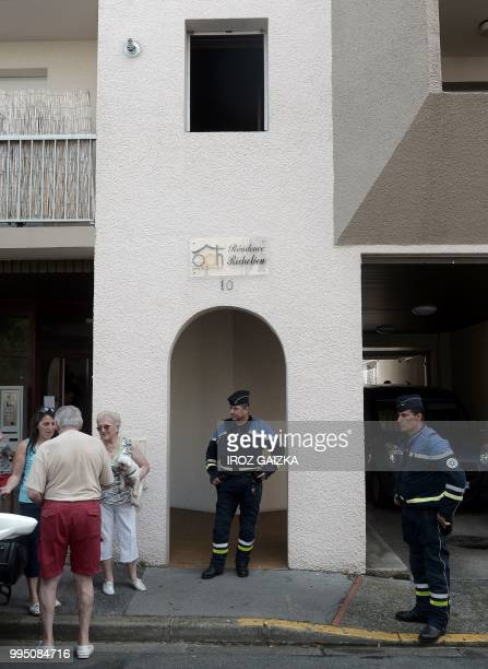Policemen and residents stand in front of a building after five people including one child were killed when a fire tore through an apartment in Pau...