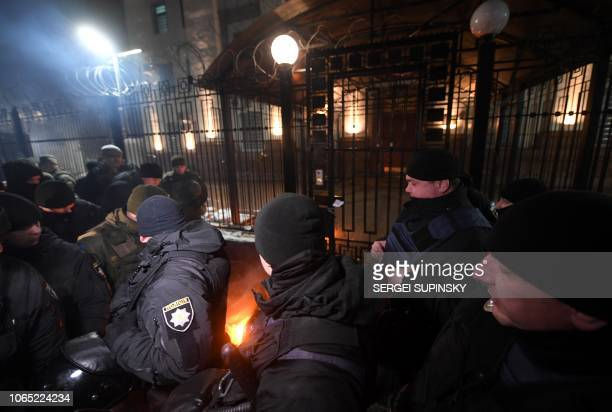 TOPSHOT Policemen and servicemen of Ukrainian National Guard extinguish a flare thrown by protesters in front of the Russian embassy in Kiev late on...