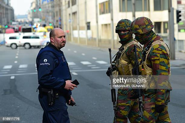 Policemen and soldier stand guard at the entrance of a security perimeter set near Maalbeek Maelbeek metro station on March 22 2016 in Brussels after...