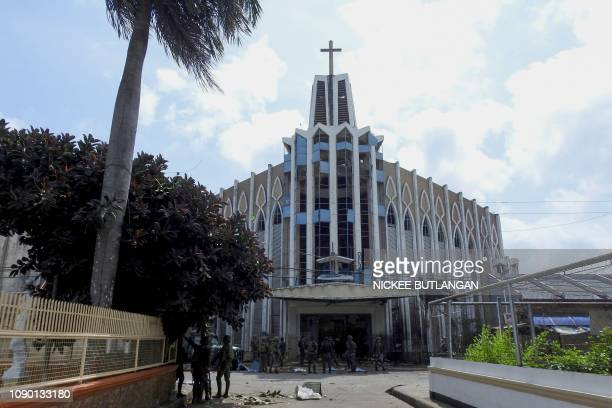 Policemen and soldiers are seen in front of a Catholic Church where the bombing took place in Jolo Sulu province on the southern island of Mindanao...