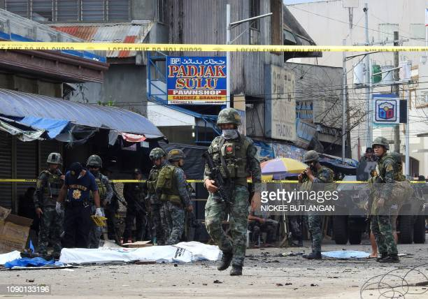 Policemen and soldiers keep watch as body bags containing the remains of blast victims as seen in a cordoned area outside a church in Jolo Sulu...